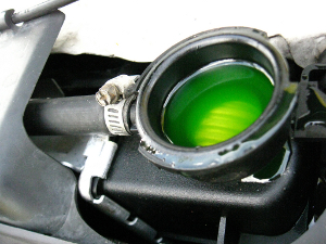 Close-up of an open car radiator. Yellow-green antifreeze is visible through the hole.