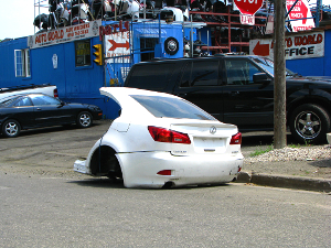The rear third of the body of a Lexus IS350 sits curbside outside an automotive shop.