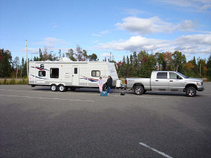 A pickup truck with travel trailer in tow.