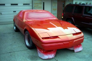 Example of a full body reapplication of automotive clear coat to a red Camaro.