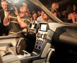 Photo taken from the interior of a car just unveiled at an auto show. Audience, camerapeople and emcees are visible.