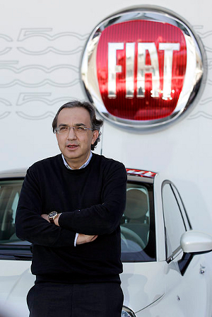 Chrysler-Fiat CEO Sergio Marchionne stands before a Fiat 500 on display at an automotive show. His arms are crossed.