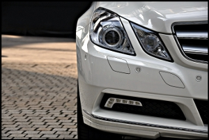 Close-up of the right headlight, grille and bumper of a white Mercedes-Benz E-class.