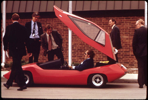 From 1973: Exhibit at the first symposium on low pollution power systems development held at the Marriott Motor Inn. Ann Arbor vehicles and hardware were assembled at the EPA Ann Arbor Laboratory. Part of the exhibit was held in the motel parking lot. This photo shows participants looking over the ESB Sundancer, an experimental electric car.