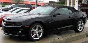 A black 2011 Chevrolet Camaro SS convertible is parked in a car lot. The top is up, and the vehicle is dotted with rainwater.