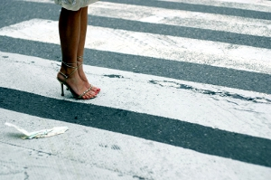 Close-up of a woman's feet in pumps, standing in the middle of a crosswalk.