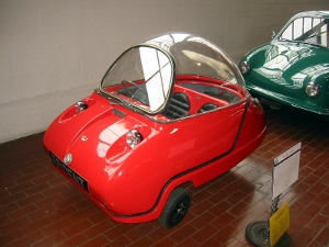 A red 1965 Peel Trident microcar that is on display in a car museum.