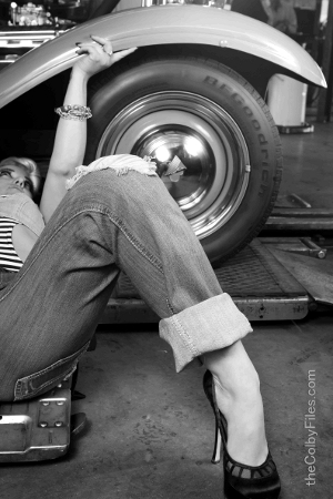 A woman in high heels works on the undercarriage of a car.