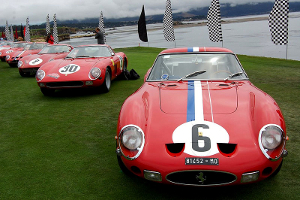 A lineup of red 1962 Ferrari 250 GTOs in a grassy area.