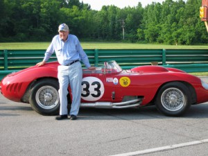 Carroll Shelby standing next to a Maserati 450S that he raced in 1957.