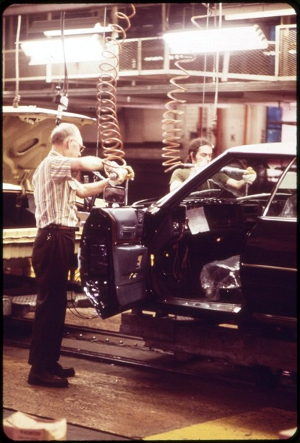 INSTALLING BODY WIRING ON THE CADILLAC ASSEMBLY LINE.