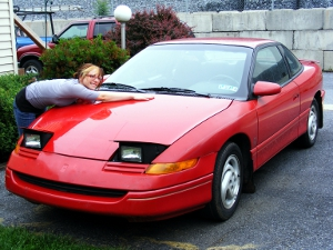 Woman leaning across the waxed hood of a red car.