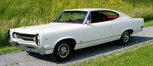 "Left front exterior view of a 1967 American Motors (AMC) automobile with side windows down. The Marlin is a two-door fastback (hardtop - no ""B-pillar"") and inished in white with red interior."