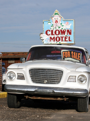 "A car is for sale outside a ""Clown Motel."""