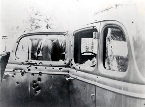Bonnie Park and Clyde Barrow's death car. Close-up taken of bullet holes in the left-side door. Of their 1934 Ford V8 sedan.