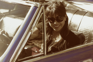 A smiling woman wearing sunglasses sits in the driver's seat of a convertible car.