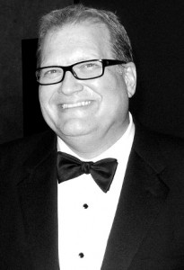 Black-and-white photo of comedian Drew Carey at a black-tie event.