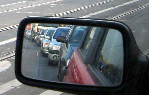 Side mirror view of a line of cars behind the lead car. It's a traffic jam.