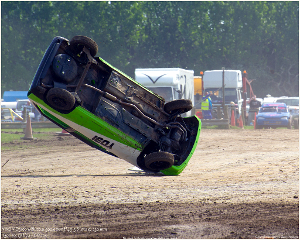A car flipping over on dirt.