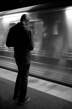 A man texting while walking in the vicinity of a speeding subway train.